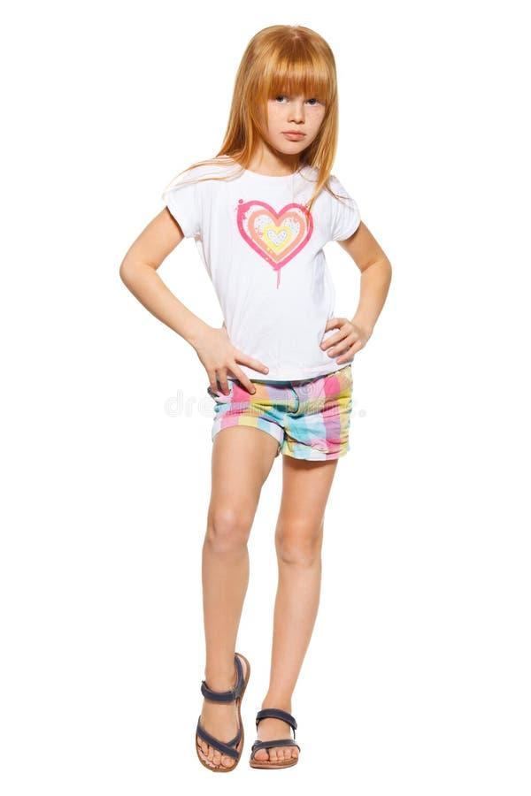 Pełna długości dziewczyna z czerwonym włosy w skrótach i koszulce troszkę; odizolowywający na białym tle zdjęcie royalty free