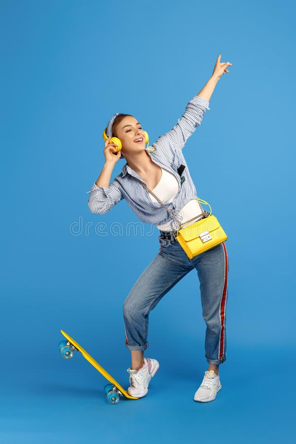 Pełna długości fotografia dosyć beztroska młoda kobieta słucha muzykę z żółtymi hełmofonami z centem lub deskorolka zdjęcia stock