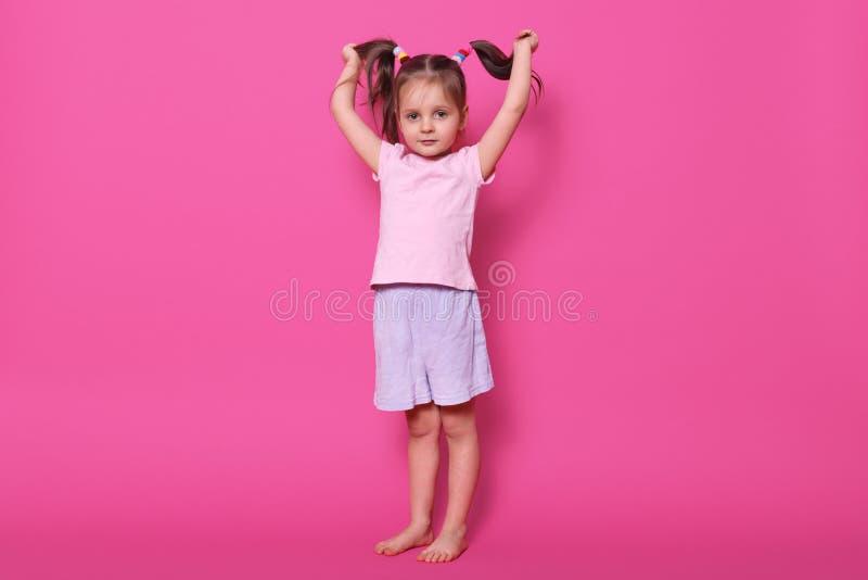 Pełna długości fotografia mała powabna dziewczyna w fotografii studiu przeciw menchii ścianie Śliczna kobieta trzyma jej śmieszny obrazy royalty free