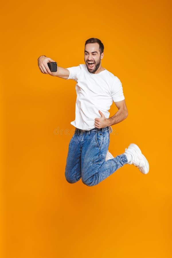 Pełna długości fotografia piękny facet 30s w przypadkowej odzieży śmia się selfie na telefonie komórkowym i bierze, odizolowywają zdjęcia stock