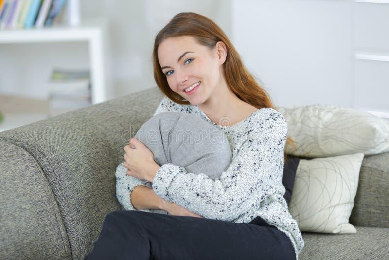 Pełna długości młodej kobiety mienia poduszka na kanapie obraz stock