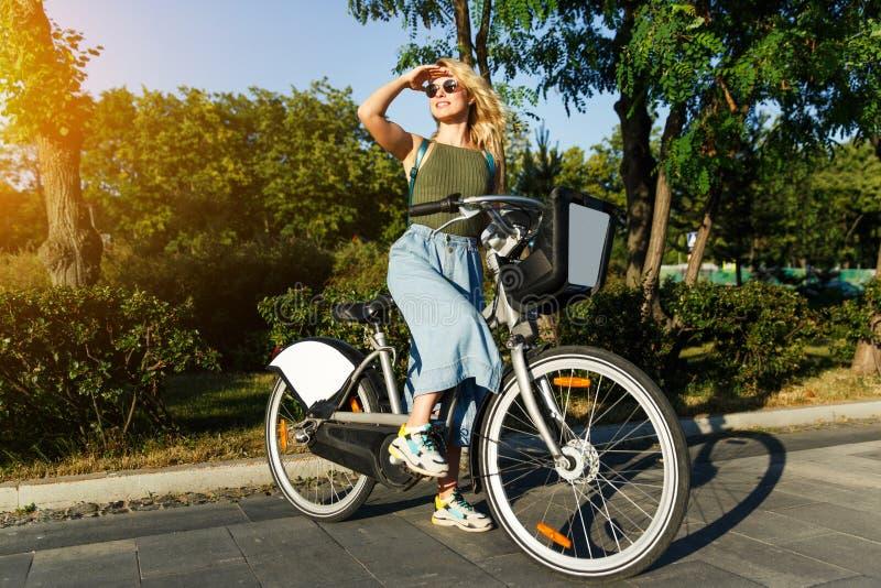 Pełna fotografia blondynka patrzeje stronę w długiej drelich spódnicy pozycji na rowerze obok zielonych krzaków wewnątrz w okular obraz stock