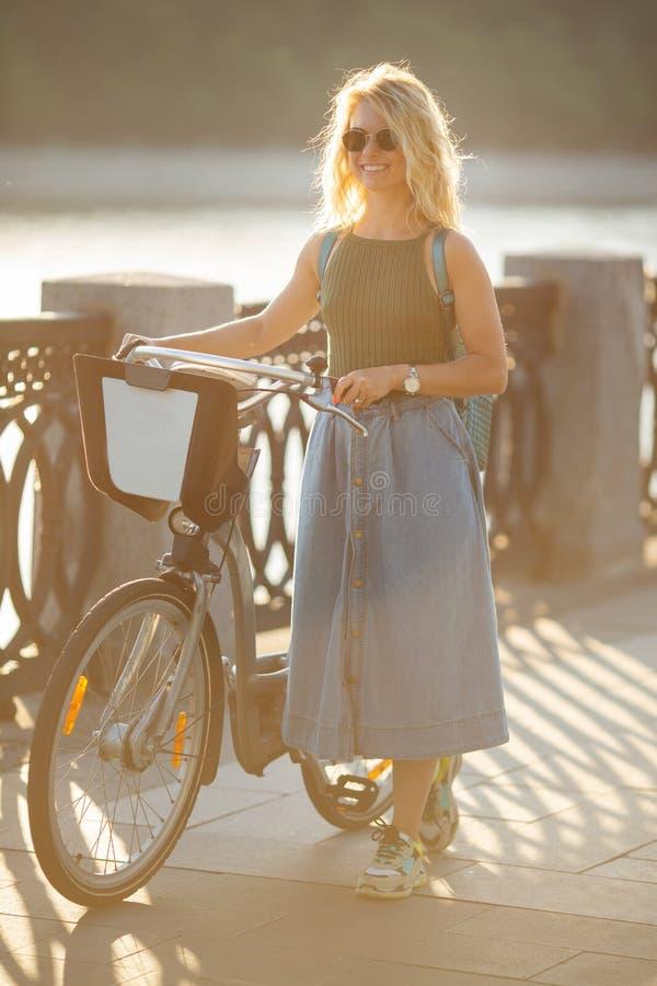 Pełna fotografia patrzeje stronę w drelich spódnicy pozycji obok roweru na moście w mieście kędzierzawa blondynka zdjęcie royalty free