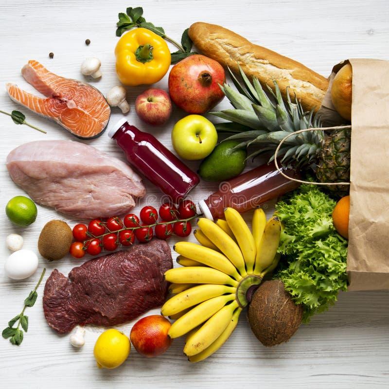 Pełna papierowa torba zdrowy surowy jedzenie na białym drewnianym tle Kulinarny karmowy tło Lay świeże owoc, veggies, zielenie, obraz royalty free