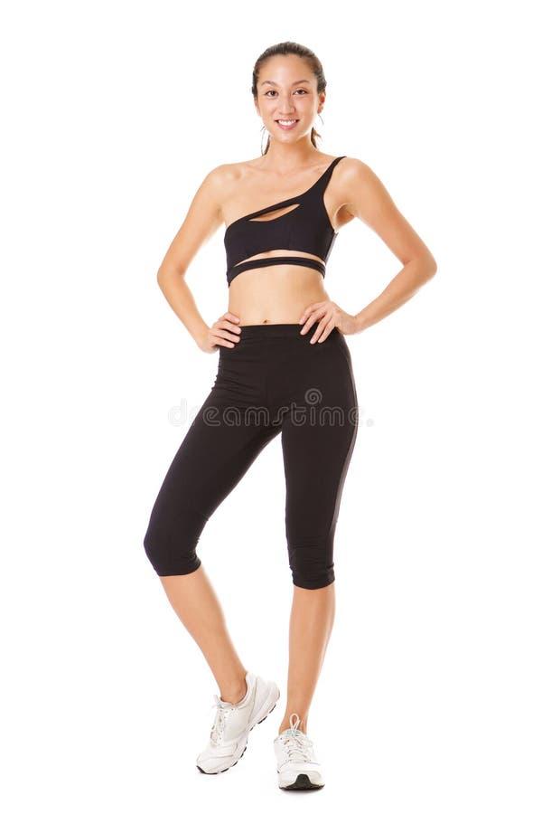 Pełnego ciała atrakcyjna młoda azjatykcia kobieta pozuje w sporty stroju przeciw odosobnionemu białemu tłu fotografia stock