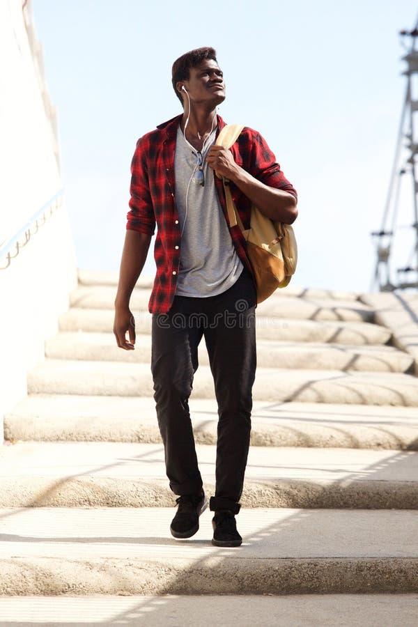 Pełnego ciała chłodno młody człowiek z torby odprowadzenia puszkiem kroki i patrzeć daleko od zdjęcie royalty free