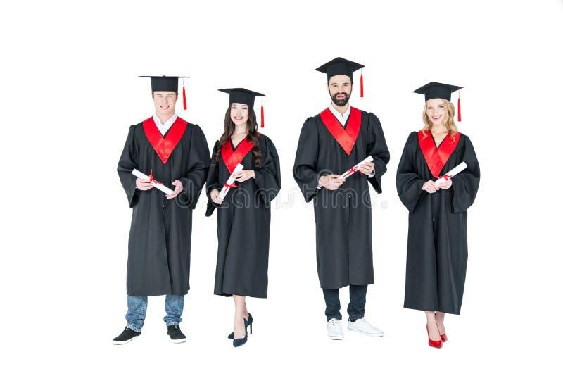 Pełnej długości frontowy widok szczęśliwi ucznie w skalowaniu nakrywa mienie dyplomy zdjęcie stock
