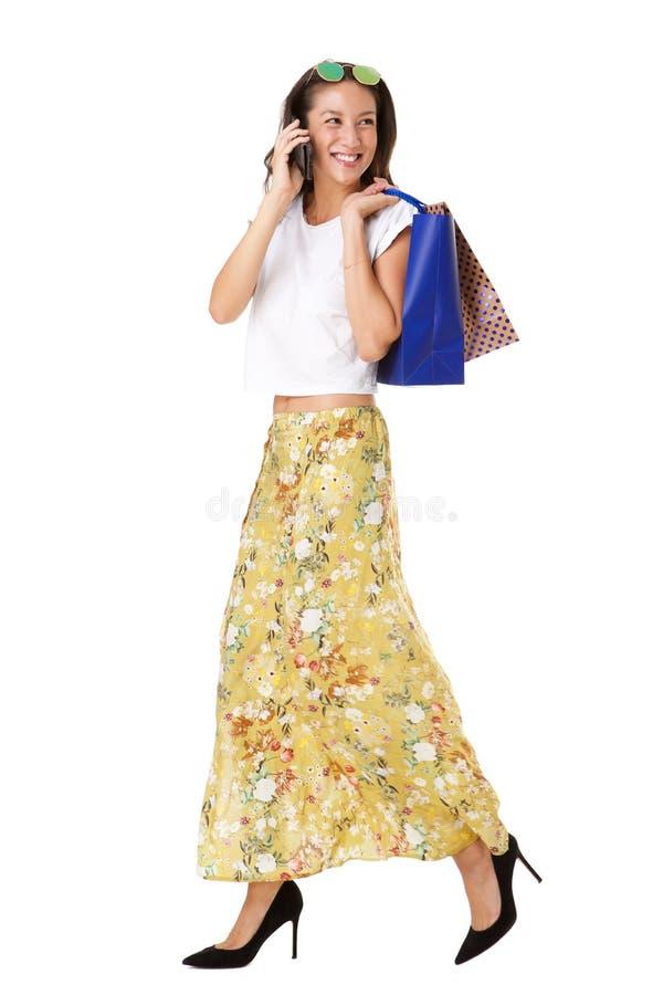 Pełnej długości piękna młoda azjatykcia kobieta chodzi i opowiada na telefonie komórkowym z torbami na zakupy fotografia stock