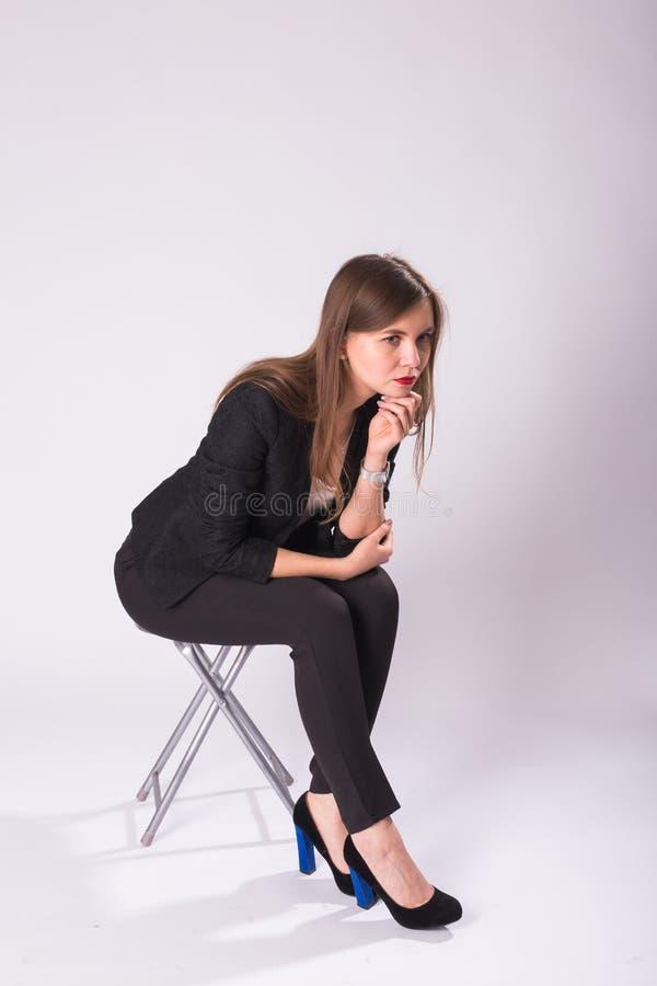 Pełnej długości pracowniany portret młoda biznesowa kobieta w czarnym kostiumu, szpilki buty, siedzi w krześle na białym tle zdjęcia royalty free