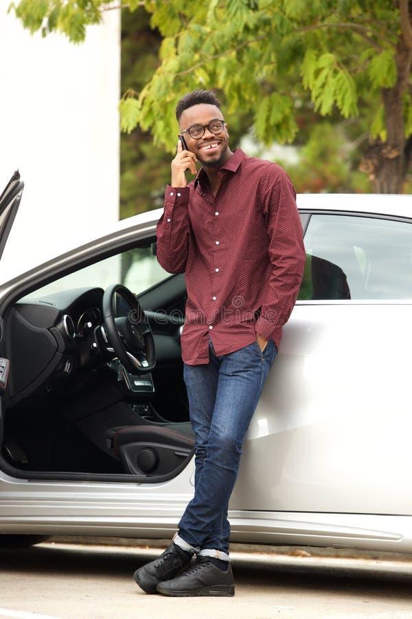 Pełnej długości przystojny murzyn opowiada na telefonie komórkowym samochodem zdjęcia stock