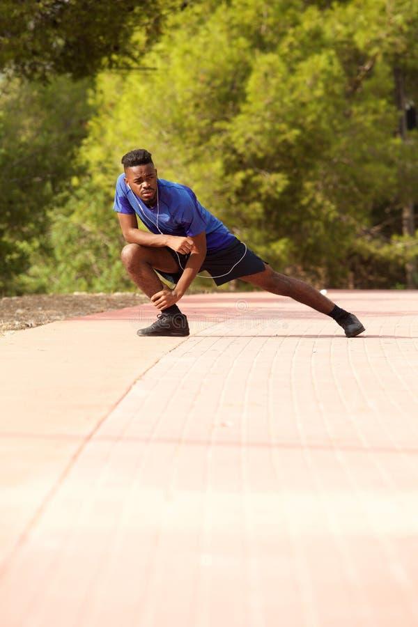 Pełnej długości sporty murzyn robi ćwiczeniu rozciąga outside zdjęcia stock