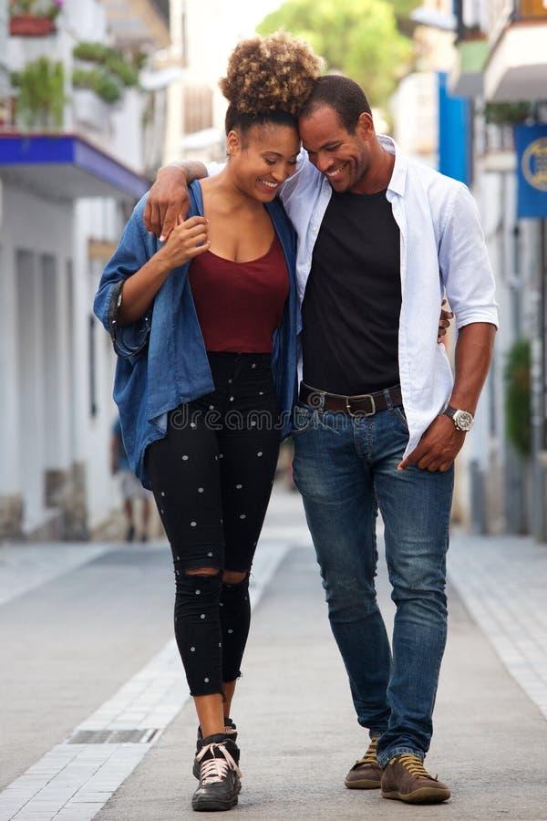Pełnej długości szczęśliwa atrakcyjna para chodzi wpólnie na dacie na ulicie obrazy stock