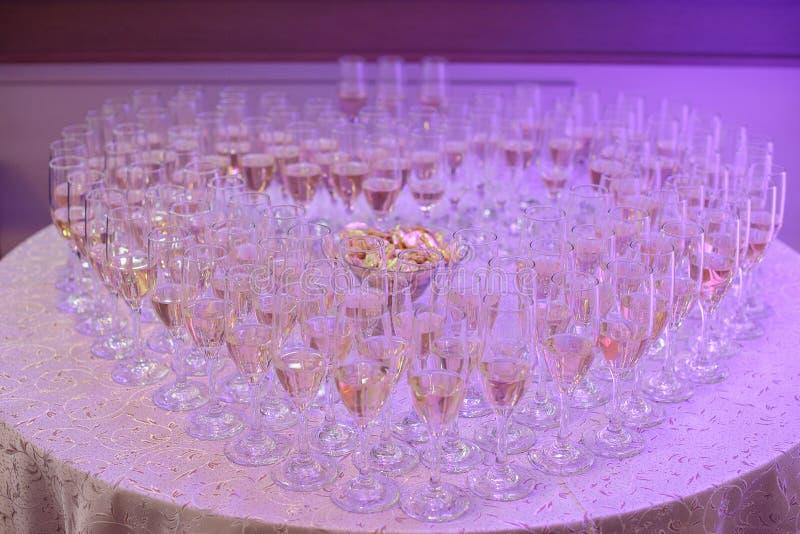Pełni szkła żywy lub szampan tworzy kierowego kształt, ustawiający na round stole pod neonowym purpurowym ligh obrazy stock