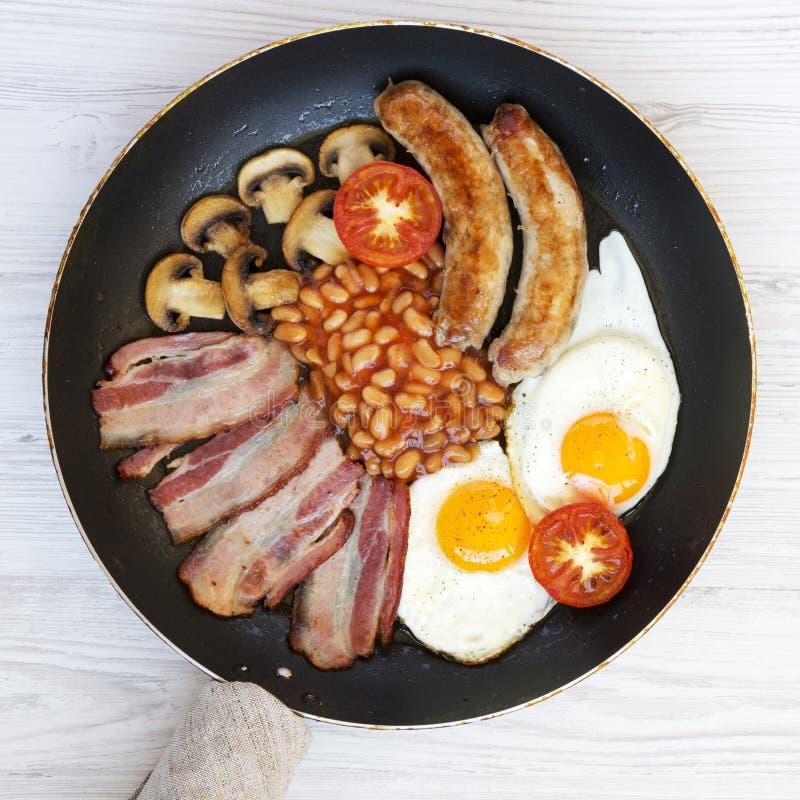 Pełny Angielski śniadanie w kulinarnej niecce z kiełbasami, smażącymi jajkami, fasolami i bekonem na białym drewnianym stole, odg zdjęcie stock