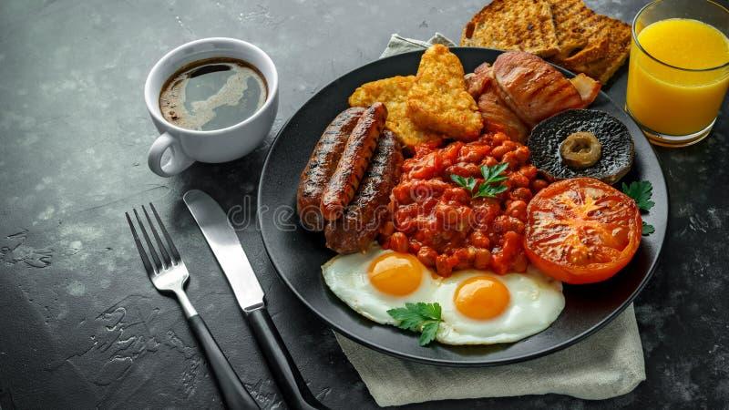 Pełny Angielski śniadanie z bekonem, kiełbasa, smażył jajko, piec fasole, hash i pieczarki w czarnym talerzu, - brązy Filiżanki c obraz stock