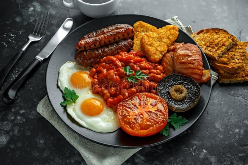 Pełny Angielski śniadanie z bekonem, kiełbasa, smażył jajko, piec fasole, hash i pieczarki w czarnym talerzu, - brązy Filiżanki k zdjęcia stock