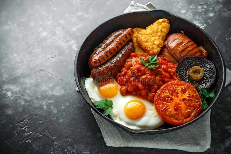 Pełny Angielski śniadanie z bekonem, kiełbasa, smażył jajko, piec fasole, hash i pieczarki w nieociosanej rynience, - brązy, niec zdjęcia stock