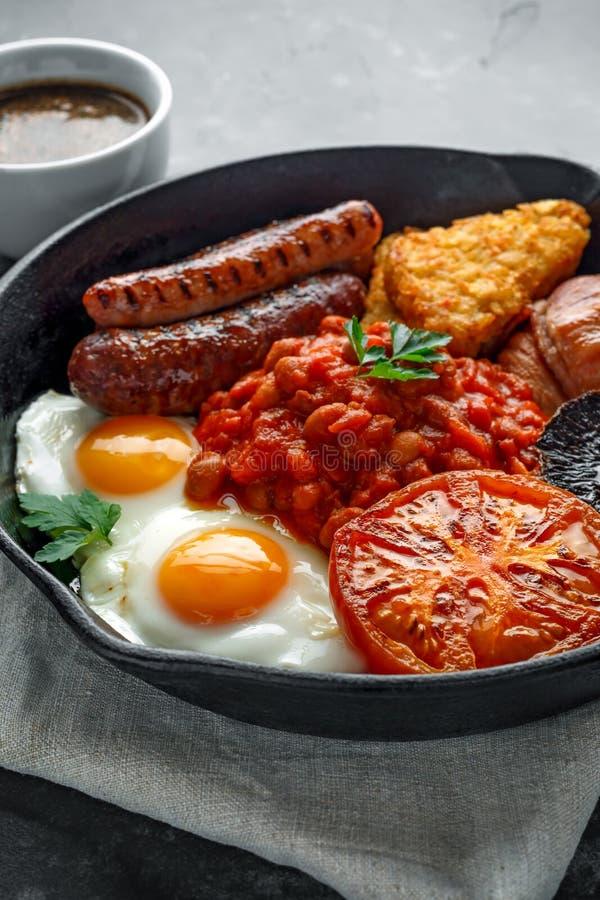 Pełny Angielski śniadanie z bekonem, kiełbasa, smażył jajko, piec fasole, hash i pieczarki w nieociosanej rynience, - brązy, niec obraz royalty free