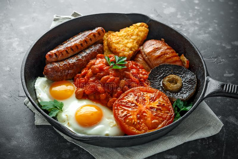 Pełny Angielski śniadanie z bekonem, kiełbasa, smażył jajko, piec fasole, hash i pieczarki w nieociosanej rynience, - brązy, niec obraz stock