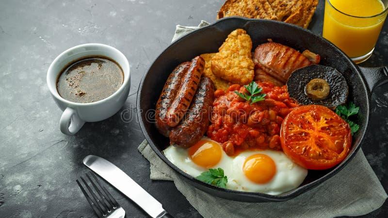 Pełny Angielski śniadanie z bekonem, kiełbasa, smażył jajko, piec fasole, hash i pieczarki w nieociosanej rynience, - brązy, niec zdjęcie royalty free