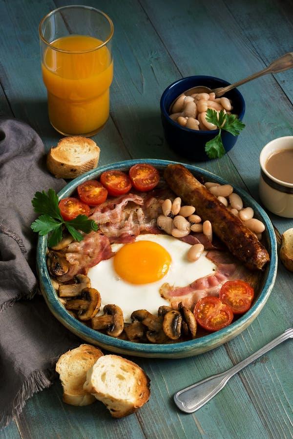 Pełny Angielski śniadanie z rozdrapanymi jajkami, kiełbasą, pieczarkami, fasolami i bekonem na drewnianym nieociosanym zielonym s zdjęcie royalty free
