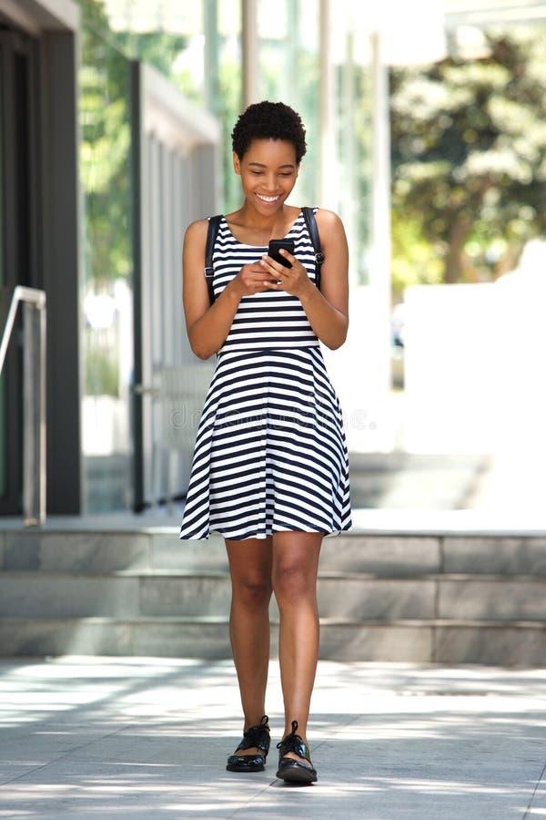 Pełny ciało młodej kobiety odprowadzenie z telefonem komórkowym w mieście fotografia stock
