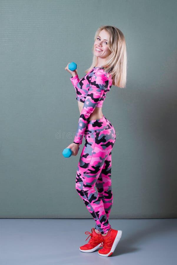 Pełny ciało portret ćwiczy z dumbbells dysponowana dziewczyna Bicepsa trening Uśmiechnięty i patrzejący kamerę fotografia royalty free