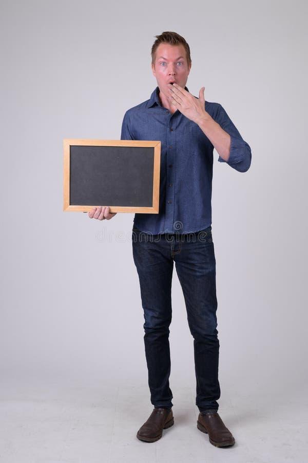 Pełny ciało strzał młody biznesmena mienia blackboard i patrzeć szokujący fotografia royalty free