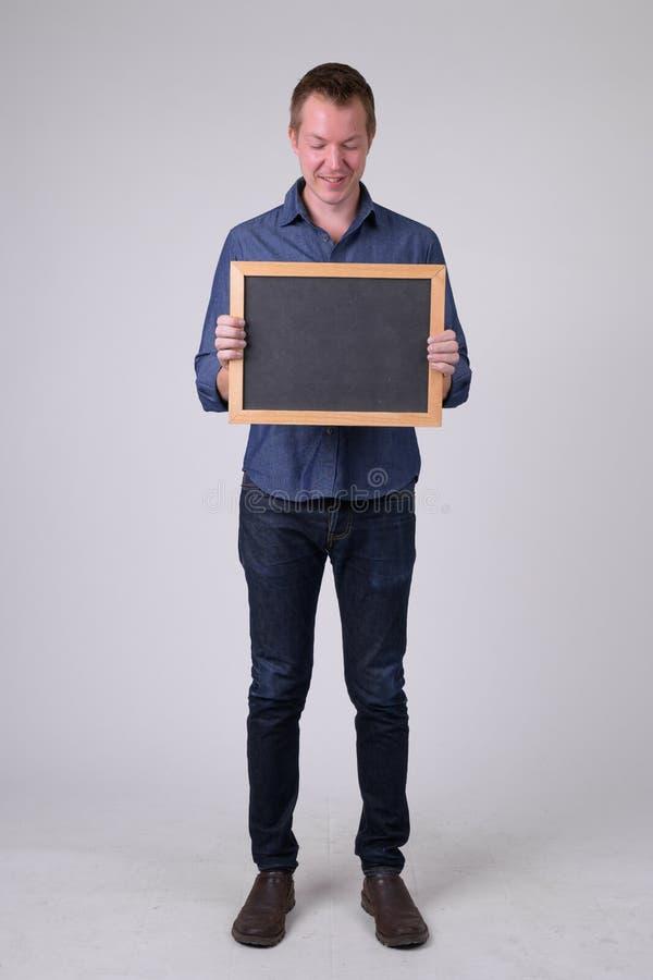 Pełny ciało strzelał szczęśliwy młody biznesmen patrzeje blackboard obraz royalty free