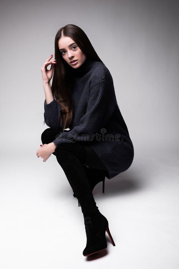 Pełny ciało widok młody moda modela obsiadanie na podłoga Odizolowywającej na bielu zdjęcia stock