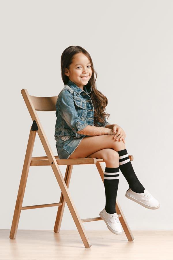 Pełny długość portret śliczny małe dziecko patrzeje kamerę i ono uśmiecha się w eleganckich cajgów ubraniach zdjęcia stock