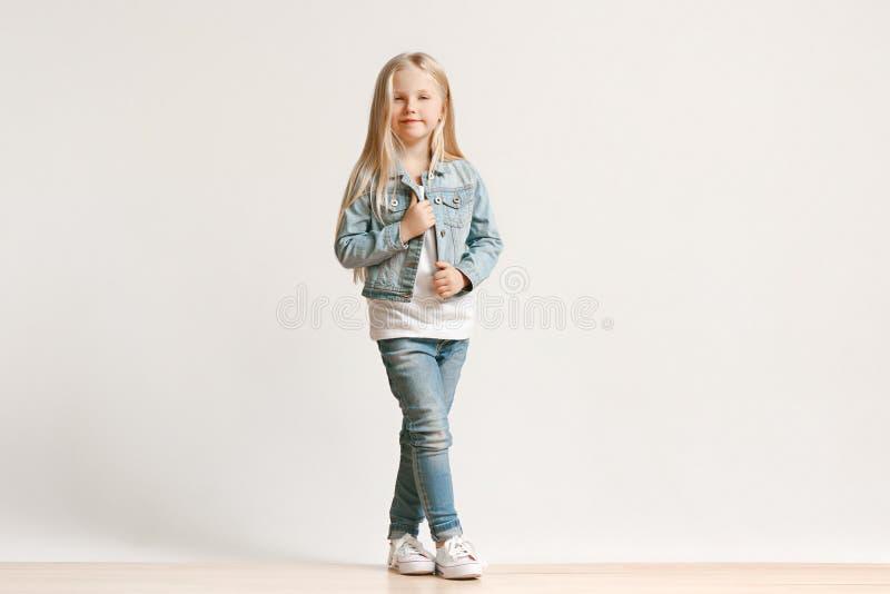 Pełny długość portret śliczny małe dziecko patrzeje kamerę i ono uśmiecha się w eleganckich cajgów ubraniach zdjęcie royalty free