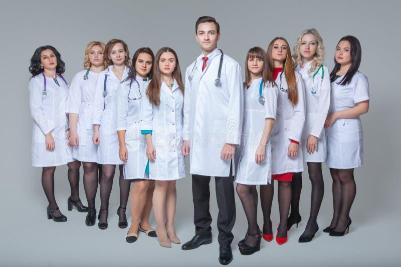 Pe?ny d?ugo?? portret atrakcyjnej samiec doktorski zostawa? przy g?ow? grupa lekarki zdjęcie royalty free