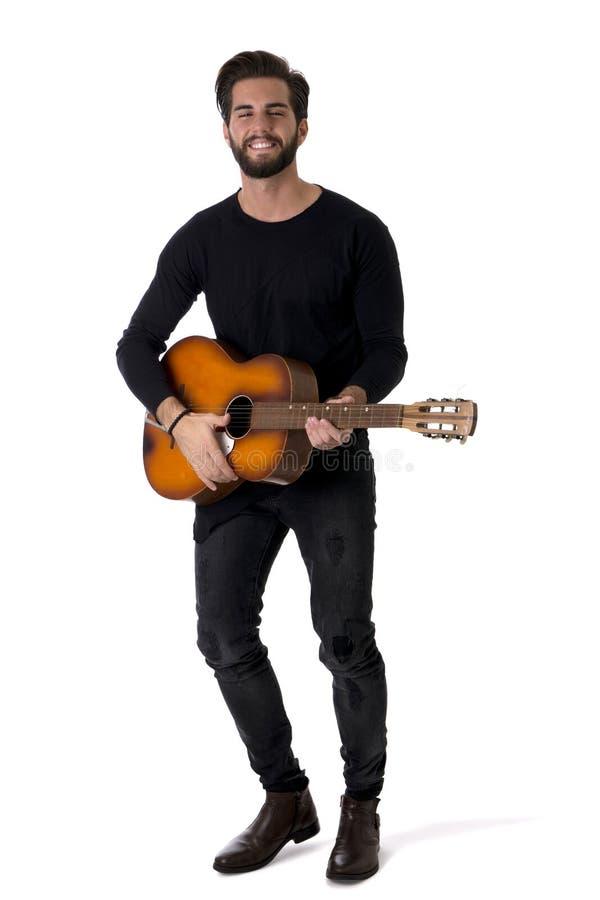 Pełny długość portret Bawić się gitarę w studiu młody człowiek zdjęcie royalty free