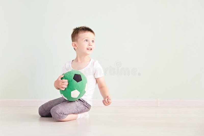 Pełny długość portret dziecko z piłki nożnej piłką odizolowywającą w domu fotografia stock