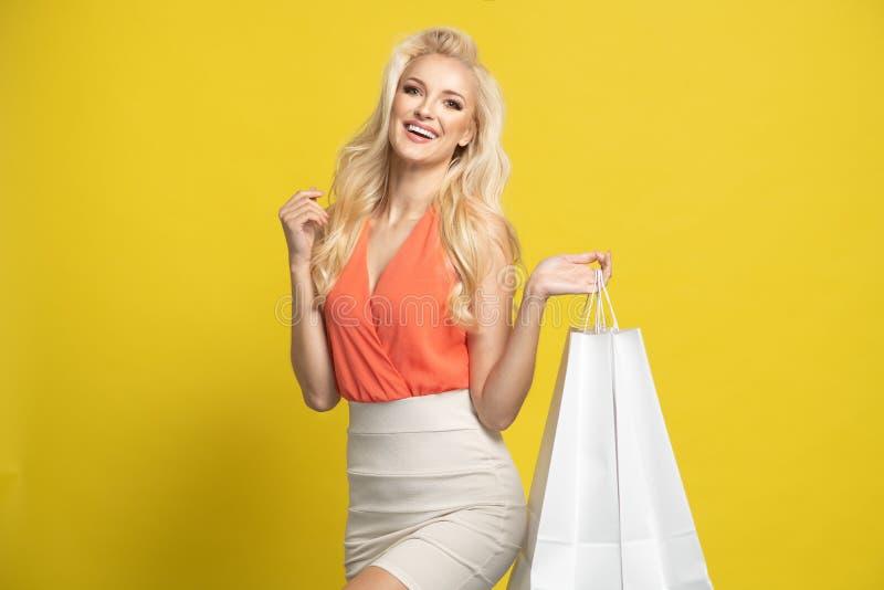 Pełny długość portret dziewczyny mienia szczęśliwe torby na zakupy odizolowywać nad żółtym tłem obrazy royalty free