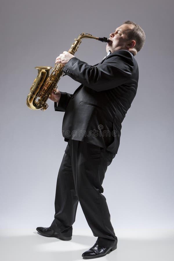 Pełny długość portret Kaukaski Dorośleć Skoncentrowanego Saksofonowego gracza Bawić się instrument zdjęcia stock