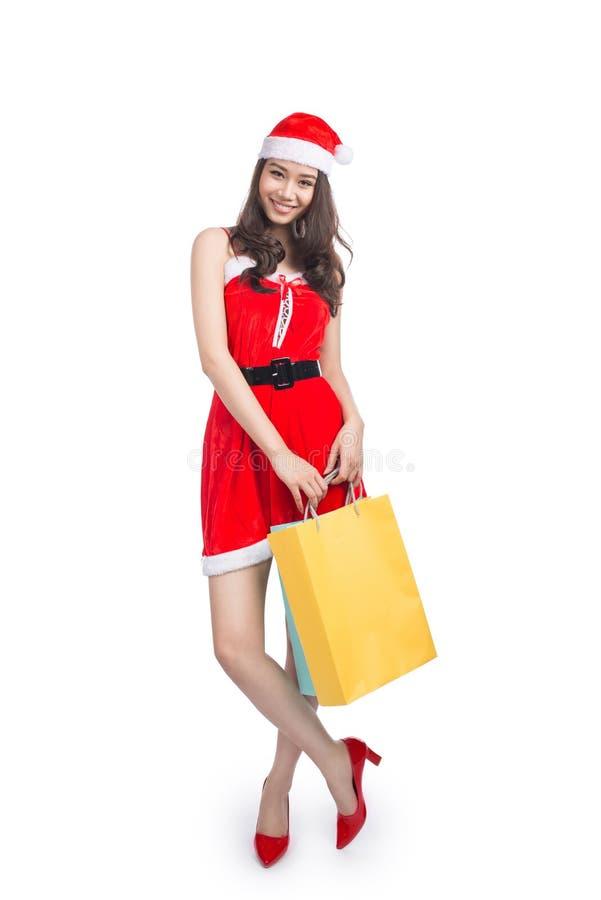 Pełny długość portret kobiety mienia młodzi uśmiechnięci azjatykci torba na zakupy przed bożymi narodzeniami obrazy royalty free