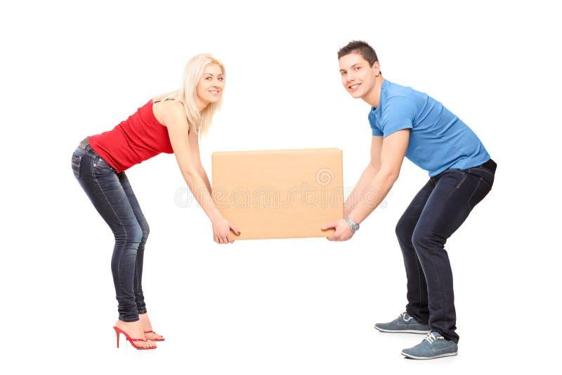 Pełny długość portret młoda para próbuje podnosić pudełko obraz stock