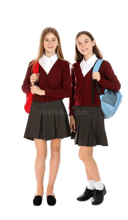 Pe?ny d?ugo?? portret nastoletnie dziewczyny w mundurku szkolnym z plecakami na bielu zdjęcie royalty free