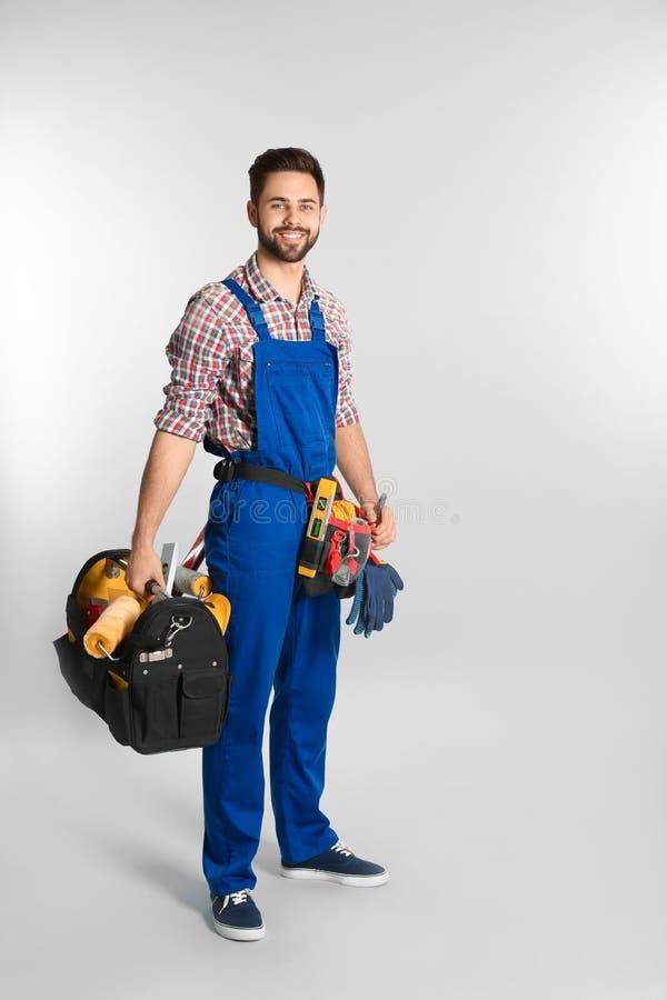 Pełny długość portret pracownik budowlany z narzędziami na lekkim tle obraz royalty free