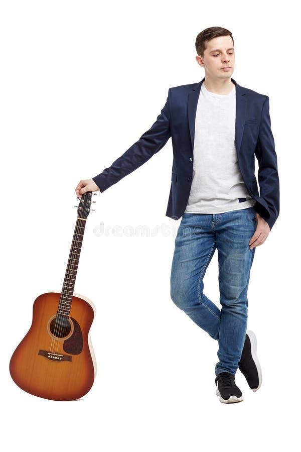 Pełny długość portret przystojna młody człowiek pozycja z gitarą obraz royalty free