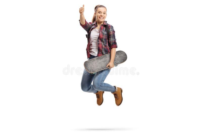 Pełny długość portret radosna nastoletnia dziewczyna z plecakiem i deskorolka robi kciukowi w górę gesta zdjęcia stock