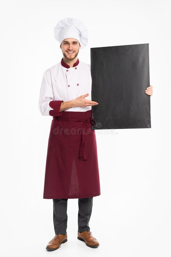 Pełny długość portret rozochocony męski szefa kuchni kucharz w jednolitej mienia pustego miejsca desce odizolowywającej na białym obrazy royalty free