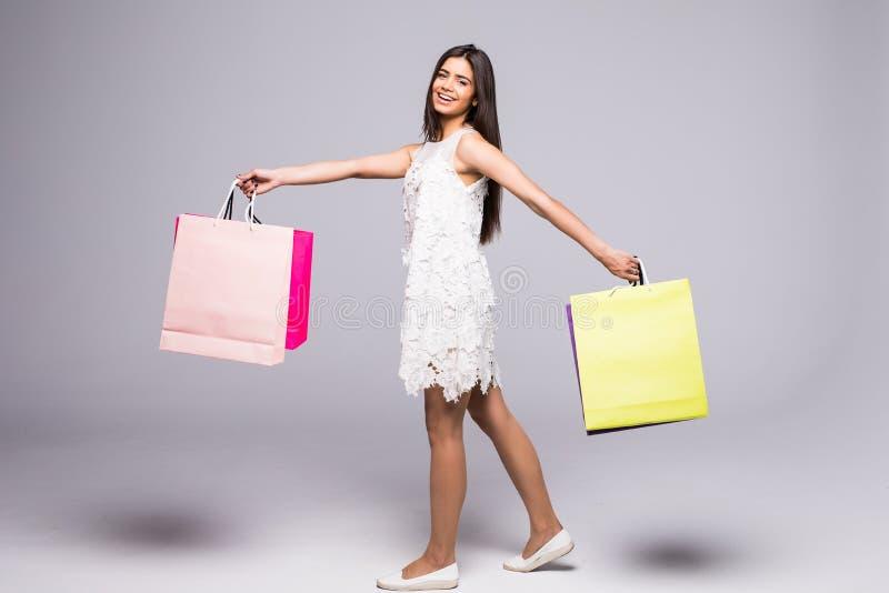 Pełny długość portret szczęśliwa z podnieceniem kobieta w smokingowej pozyci i mień kolorowych torba na zakupy odizolowywających  zdjęcia royalty free
