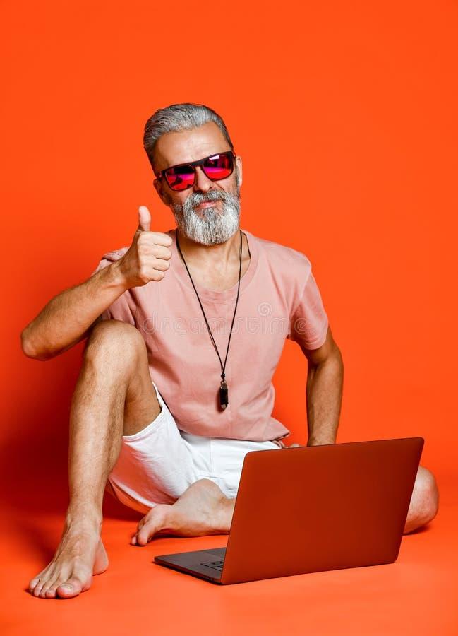 Pełny długość portret szczęśliwy stary człowiek używa laptop odizolowywającego nad pomarańczowym tłem fotografia royalty free