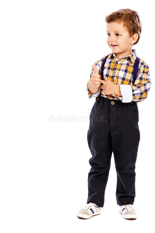 Pełny długość portret urocza chłopiec pokazuje aprobaty zdjęcia stock
