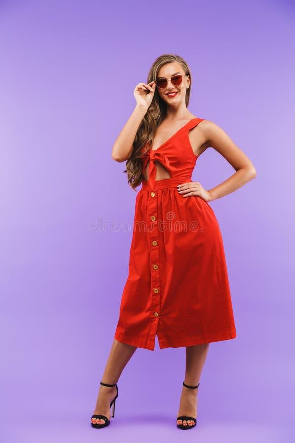 Pełny długość portret zadowolona ładna kobieta 20s jest ubranym czerwonego dre obrazy stock