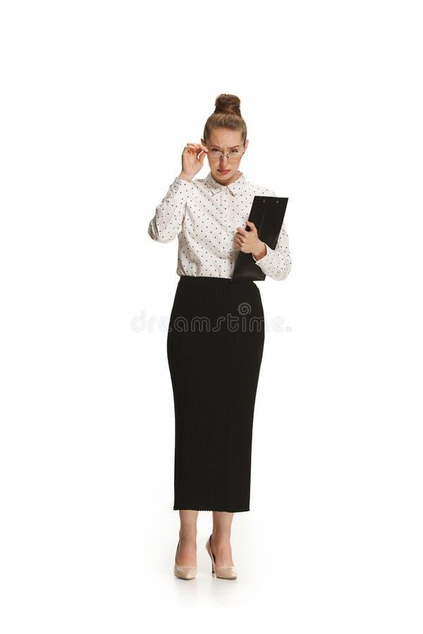 Pełny długość portret zdziwiony żeński nauczyciel trzyma falcówkę odizolowywająca przeciw białemu tłu zdjęcia stock