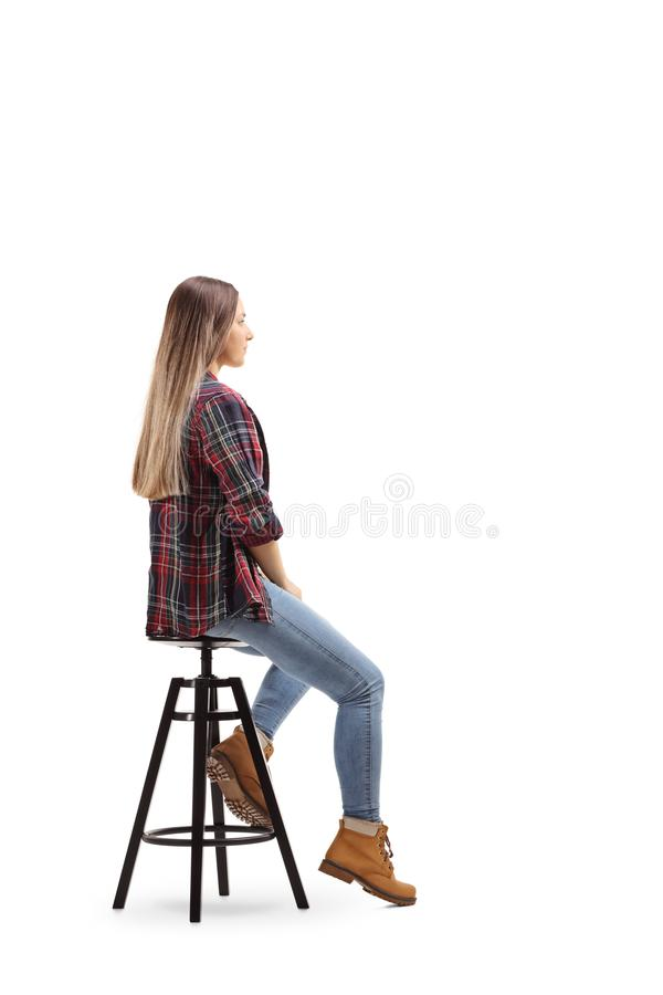 Pełny długość profilu strzał młody żeński obsiadanie na pozować i krześle zdjęcie stock